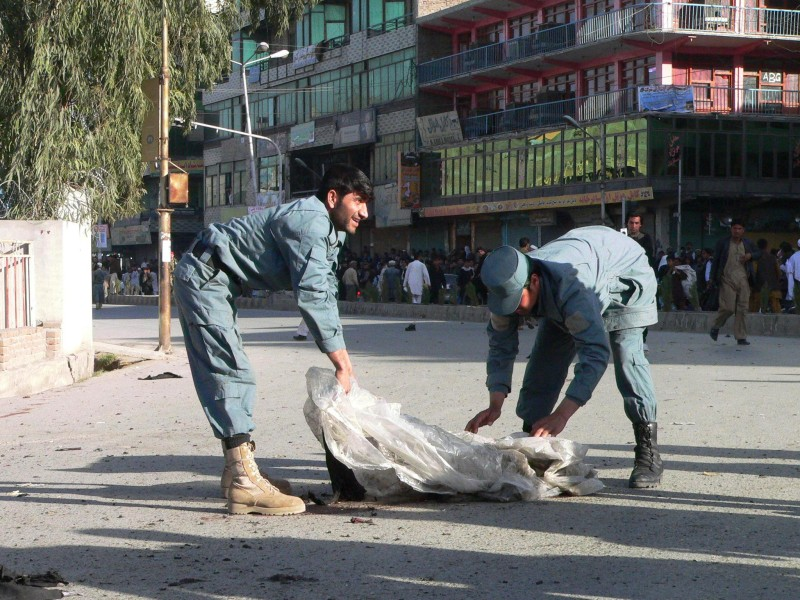 """Afghan policemen remove body parts of a suicide attacker after the bomb detonated in front of the governor's office in Jalalabad, capital of Nangarhar province on March 5, 2012. A suicide attacker wearing a suicide vest was prematurely detonated as police checked vehicles near governor's office in Jalalabad city east of capital Kabul. One NDS personels was killed and 11 people were wounded including two NDS personel and one policeman and eight civilians,"""" the interior ministry said in a statement. AFP PHOTO/Noorullah Shirzada (Photo credit should read Noorullah Shirzada/AFP/Getty Images)"""