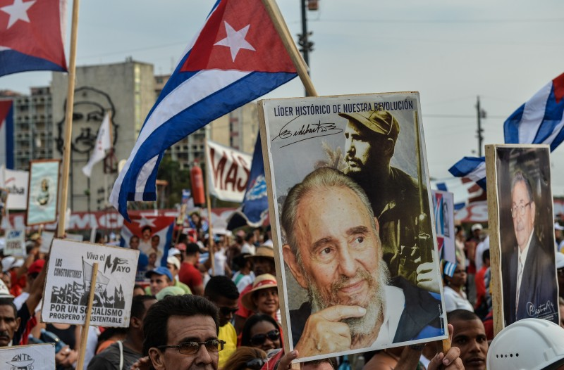 Cuban workers display a portrait of Cuban former President Fidel Castro during May Day celebrations at Revolution Square in Havana on May 1, 2013. About half a million people across Cuba took part in May Day celebrations dedicated to the late Venezuelan president Hugo Chavez, a close ally of the island's communist leaders. President Raul Castro, 81, reviewed a parade in Havana of some 300,000 people bearing banners and flags, from stands erected in the Plaza of the Revolution alongside a giant portrait of Chavez. AFP PHOTO/STR        (Photo credit should read STR/AFP/Getty Images)