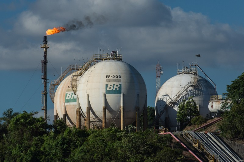 Gas tanks of Brazilian state-owned oil giant Petrobras are seen along the Negro river in Manaus, state of Amazonas, Brazil, on November 23, 2013. Manaus will host 4 matches during the FIFA World Cup 2014. AFP PHOTO / YASUYOSHI CHIBA        (Photo credit should read YASUYOSHI CHIBA/AFP/Getty Images)