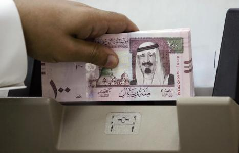 A Saudi banker counts new one hundred ri