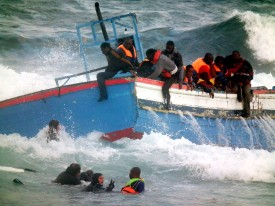 Rescuers help people in the sea after a boat carring some 250 migrants crashed into rocks as they tried to enter the port of Pantelleria, an island off the southern coast of Italy, on April 13, 2011. A fishing boat which had sailed across the Medittarenean from Libya ran aground today on rocks on the tiny Italian island of Pantelleria, killing two women, the ANSA news agency reported.  Italy is struggling to cope with a mass influx of immigrants from north Africa, many of whom risk their lives by sailing across the often stormy Medittaranean in makeshift vessels.   AFP PHOTO/ Francesco Malavolta    ==ITALY OUT== (Photo credit should read FRANCESCO MALAVOLTA/AFP/Getty Images)