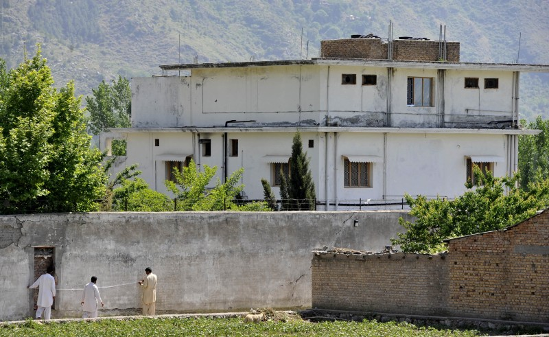 Pakistani security personnel measure a wall outside the hideout house of Al-Qaeda leader Osama bin Laden following his death by US Special Forces in a ground operation in Abbottabad on May 3, 2011. The bullet-riddled Pakistani villa that hid Osama bin Laden from the world was put under police control, as media sought to glimpse the debris left by the US raid that killed him. Bin Laden's hideout had been kept under tight army control after the dramatic raid by US special forces late May 1 in the affluent suburbs of Abbottabad, a garrison city 50 kilometres (30 miles) north of Islamabad. AFP PHOTO/ AAMIR QURESHI (Photo credit should read AAMIR QURESHI/AFP/Getty Images)