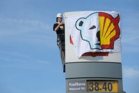 A Greenpeace activist covers the logo of the Shell oil company to protest on May 10, 2012 against the heading of the an icebreaker for Shell's Arctic oil drilling project in the north of Alaska. Environmentalists have pointed to the vastly complicated task of drilling in the harsh Arctic environment, the difficulty of effectively cleaning up any spills in such conditions, and the risks posed to wildlife and native communities in the region's fragile ecosystem.     AFP PHOTO / MICHAL CIZEK        (Photo credit should read MICHAL CIZEK/AFP/GettyImages)
