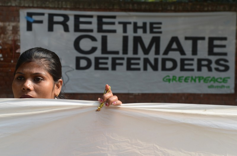 "A Greenpeace activist demonstrates during a 30-hour long protest in New Delhi on November 16, 2013, to demand the release of a group of Greenpeace activists being held in Russia. The so-called ""Arctic 30"" were detained when the Russian Coast Guard boarded their Dutch-flagged Greenpeace vessel after several activists scaled a state-owned oil platform on September 18 in a protest. AFP PHOTO/RAVEENDRAN        (Photo credit should read RAVEENDRAN/AFP/Getty Images)"