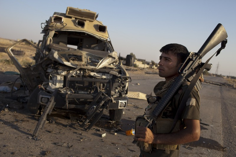 A Kurdish Peshmerga fighter, with an image of the US flag sewn onto his shirt sleeve, stands next to an ambulance destroyed due to an improvised explosive device (IED) in Hossein, during the clashes on the road to Jalawla, on August 23, 2014. The United States launched an air campaign against IS in Iraq on April 8, and has since carried out more than 90 strikes that have largely been in support of Kurdish forces in the north, drawing calls for operations elsewhere in the country. AFP PHOTO / JM LOPEZ        (Photo credit should read JM LOPEZ/AFP/Getty Images)