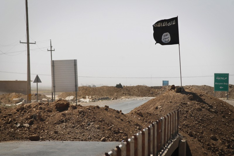 A flag of the Islamic State (IS) is seen on the other side of a bridge at the frontline of fighting between Kurdish Peshmerga fighters and Islamist militants in Rashad, on the road between Kirkuk and Tikrit, on September 11, 2014.  Ten Arab states, including heavyweight Saudi Arabia, agreed today in Jeddah to rally behind Washington in the fight against Islamic State jihadists, as it seeks to build an international coalition.   AFP PHOTO/JM LOPEZ        (Photo credit should read JM LOPEZ/AFP/Getty Images)