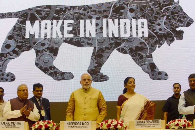 "Indian Prime Miniser Narendra Modi (C) launches the ""Make In India"" project as Minister for Commerce and Industry Nirmala Sitaraman looks on in New Delhi on September 25, 2014. Prime Minister Narendra Modi pledged September 25 to slash red tape and harness the benefits of a huge young population as he launched a campaign to attract global business to manufacture in India. India's business-friendly new leader wants to revive his country's flagging economic fortunes by kickstarting a manufacturing sector long eclipsed by that of neighbouring China.  AFP PHOTO/RAVEENDRAN        (Photo credit should read RAVEENDRAN/AFP/Getty Images)"