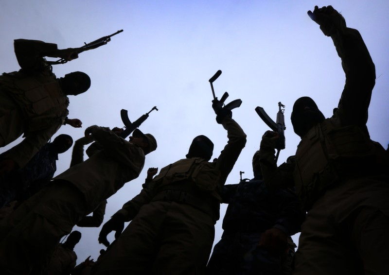 Iraqi policemen raise their weapons during a training session at a camp in the Bardarash district, 30 kilometres northeast of Mosul on January 10, 2015 as they prepare to recapture the northern Iraqi city of Mosul, currently under the control of Islamic State (IS) group fighters. IS spearheaded a sweeping militant offensive in June that overran large areas north and west of Baghdad, and also holds significant territory in Iraq and Syria. AFP PHOTO / SAFIN HAMED        (Photo credit should read SAFIN HAMED/AFP/Getty Images)