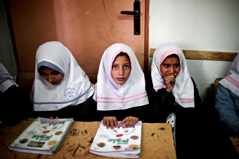 Afghan schoolgirls attend a class at the Shahid Nasseri refugee camp in Taraz Nahid village near the city of Saveh, some 130 kms southwest of the capital Tehran, on February 8, 2015. Some 5000 Afghan refugees live at the camp which is run by the Iranian Bureau for Aliens and Foreign Immigrants' Affairs (BAFIA), the World Food Program (WFP) and UNHCR. According to the United Nations High Commissioner for Refugees (UNHCR), there are 950,000 registered Afghan residents in Iran -- some of whom have never even set foot in their homeland -- but interior ministry estimates around three million Afghans living in the Islamic republic. AFP PHOTO / BEHROUZ MEHRI        (Photo credit should read BEHROUZ MEHRI/AFP/Getty Images)