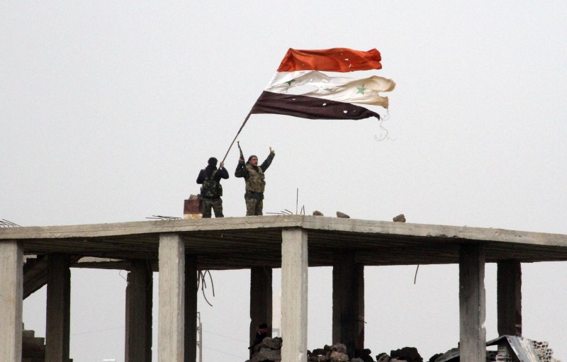 Syrian government forces wave the Syrian flag while standing on top of a building in Deir al-Adas in the Daraa province on February 11, 2015 after President Bashar al-Assad's army, backed by Hezbollah and Iranian officers, pushed rebels out of the area. Lebanon's Hezbollah, Syrian regime forces and Iranian officers fighting rebels in southern Syria have advanced to the edge of Israeli-occupied territory, a monitor and state media said. Daraa is located near Damascus, the border with Jordan as well as the Golan Heights.  AFP PHOTO / STR        (Photo credit should read STR/AFP/Getty Images)