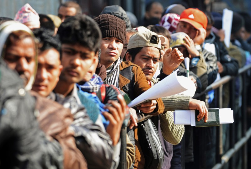 Nepalese migrant workers queue to receive official documents in order to leave Nepal from the Labour department in Kathmandu on January 27, 2014.  Nearly 200 Nepali migrant workers died in Qatar in 2013, many of them from heart failure, officials said, figures that highlight the grim plight of labourers in the Gulf nation.   AFP PHOTO/Prakash MATHEMA        (Photo credit should read PRAKASH MATHEMA/AFP/Getty Images)