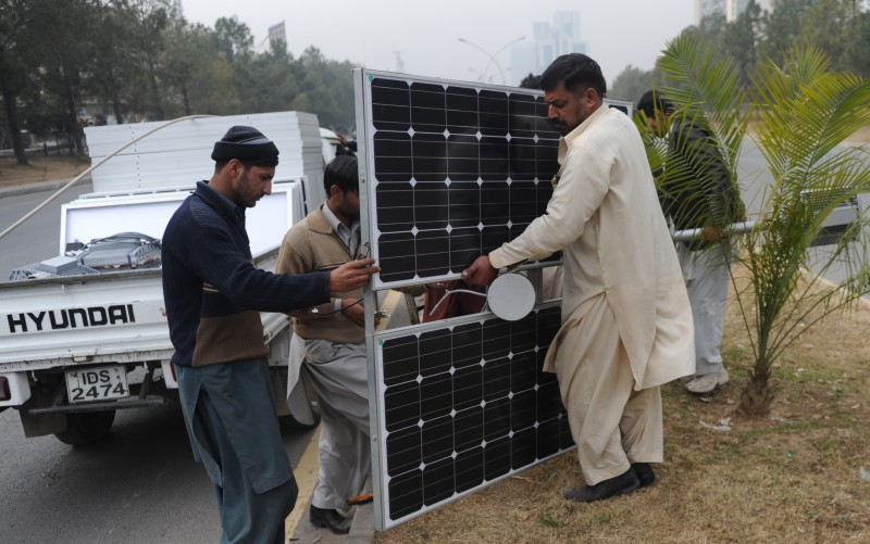 Pakistani workers prepare solar energy light panels on a road divider in Islamabad on February 2, 2014. The country faces an electricity shortfall of around 4,000 megawatts in the sweltering summer, leading to lengthy blackouts that can make the lives of the population a misery and have strangled economic growth. AFP PHOTO/Aamir QURESHI        (Photo credit should read AAMIR QURESHI/AFP/Getty Images)