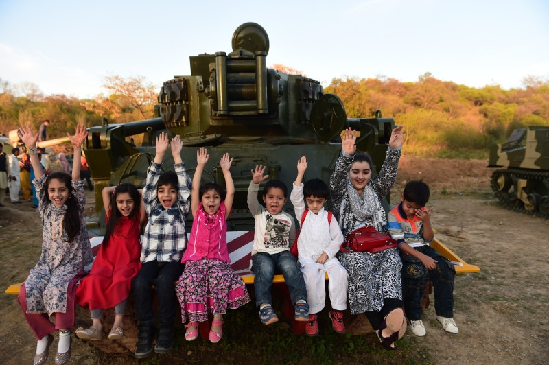 Pakistani children sit on a tank as they enjoy the park during a public holiday ahead of National Day celebration in Rawalpindi on March 22, 2015.  AFP PHOTO / Farooq NAEEM        (Photo credit should read FAROOQ NAEEM/AFP/Getty Images)
