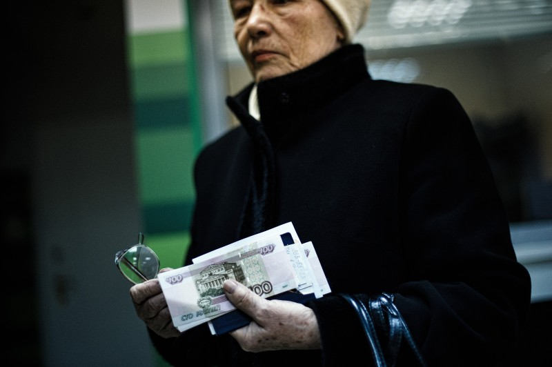 An elderly woman holds her pension received in Russian ruble notes in the eastern Ukrainian city of Donetsk on April 1, 2015. The year-long conflict in east Ukraine has closed businesses across the industrial heartland, ramping up unemployment, crippling its financial sector and leaving it ever more reliant on Moscow.    AFP PHOTO / DIMITAR DILKOFF        (Photo credit should read DIMITAR DILKOFF/AFP/Getty Images)