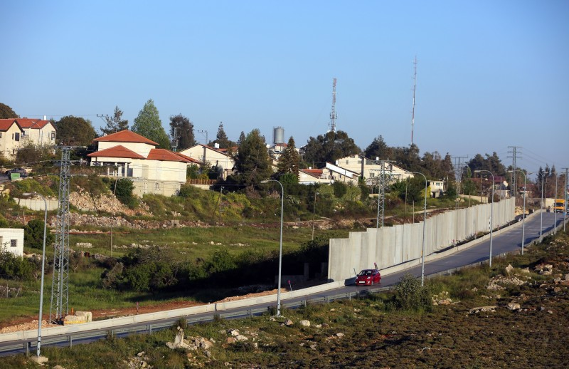 A car drives, on a road used by Palestinians from the adjacent Jalazon refugee camp, past the new defensive wall that surrounds the Israeli settlement of Beit El, in the occupied West Bank north of Ramallah on April 7, 2015. AFP PHOTO/ABBAS MOMANI        (Photo credit should read ABBAS MOMANI/AFP/Getty Images)