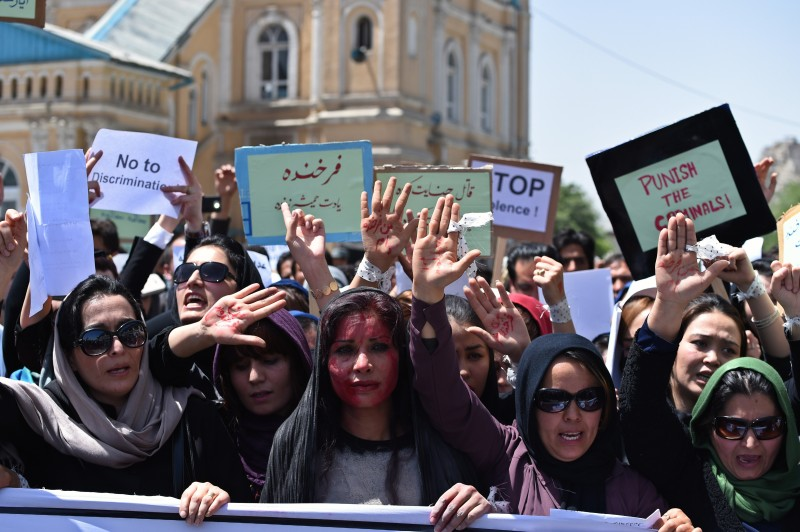 Afghan artists march after performing a role play on April 27, 2015 to depict the lynching of Afghan woman Farkhunda, 27, who was attacked by an angry mob, in Kabul. Farkhunda was beaten with sticks and stones, thrown from a roof, before being run over by a car outside a mosque in Kabul on March 19. The mob then set her body ablaze and dumped it in a river as police allegedly looked on. AFP PHOTO / SHAH Marai        (Photo credit should read SHAH MARAI/AFP/Getty Images)