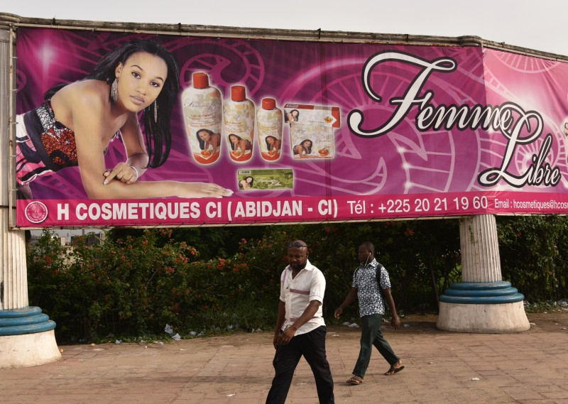 Two men walk under a giant advertising placard of skin-lightening products in Abidjan on May 2, 2015. Ivory Coast's government has forbidden the use of skin whitening products, popular among Ivorian women, the Health Ministry announced on May 6, 2015.  AFP PHOTO / SIA KAMBOU        (Photo credit should read SIA KAMBOU/AFP/Getty Images)