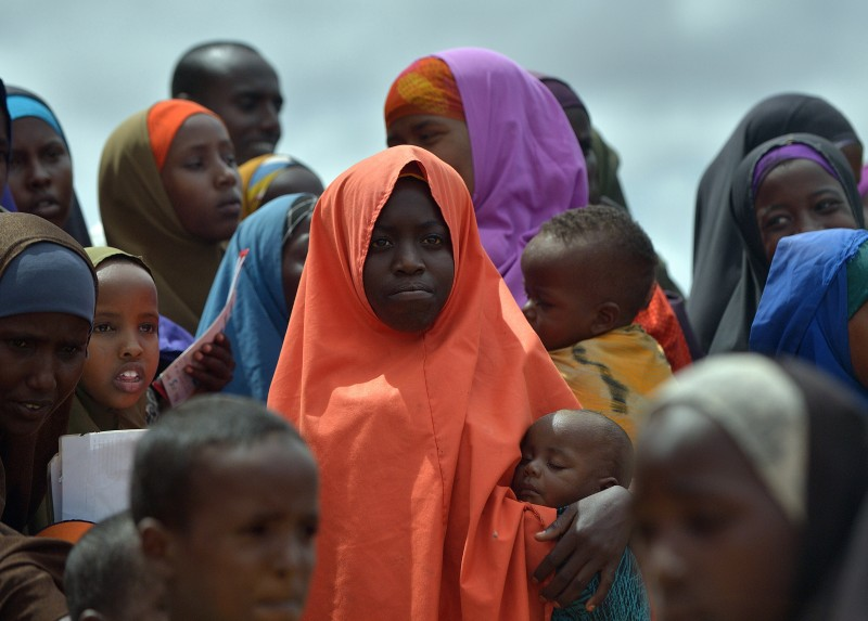 Refugees gather to watch the arrival of United Nations High Commissioner for Refugees Antonio Guterres at IFO-2 complex of the sprawling Dadaab refugee camp on May 8, 2015. Dadaab refugee camp currently houses some 350,000 people and for more than 20 years has been home to generations of Somalis who have fled their homeland wracked by conflicts. But Kenya's government asked the UN refugee agency (UNHCR) to close the camp after an attack on Kenyas Garissa University by Somalia-based Al-Shabaab gunmen in April, whom are suspected to have planned and launched their attack from the camp.  AFP PHOTO / TONY KARUMBA        (Photo credit should read TONY KARUMBA/AFP/Getty Images)