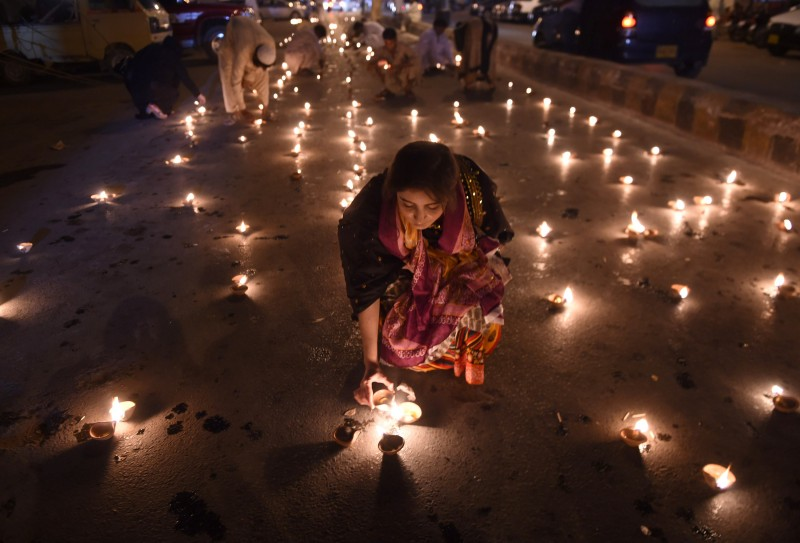 An activist of Pakistan Muslim League-Q lights oil lamps during a vigil for the victims of an attack by gunmen on a Shiite Ismaili minority bus, in Karachi on May 15, 2015. The United States offered to help Pakistan investigate a deadly Karachi bus attack which left 44 Shiite Ismailis dead, in the first assault in the country claimed by the Islamic State group.   AFP PHOTO/ Asif HASSAN        (Photo credit should read ASIF HASSAN/AFP/Getty Images)