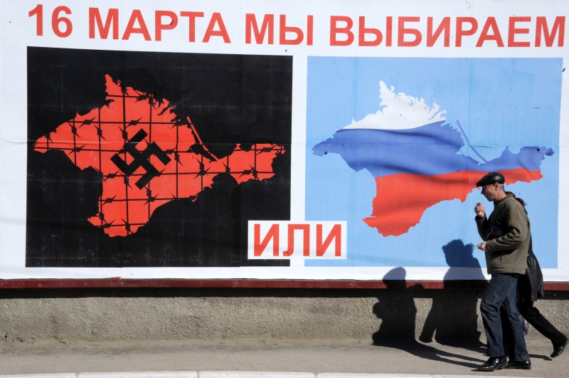 "A man walks past a poster in Sevastopol on March 13, 2014 reading ""On March 16 we will choose either... or..."", depicting Crimea in red with a swastika and covered in barbed wire (L) and Crimea with the colors of the Russian flag. Losing Crimea could result in millions in banking losses for the mainland, Ukraine's central bank governor warned on March 13, as the autonomous region looked likely to vote to join Russia in a weekend referendum.     AFP PHOTO/ VIKTOR DRACHEV        (Photo credit should read VIKTOR DRACHEV/AFP/Getty Images)"