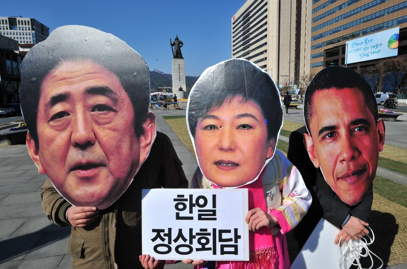"South Korean activists wear the masks of South Korean President Park Geun-Hye (C), Japanese Prime Minister Shinzo Abe (L) and US President Barack Obama (R) during an anti-government protest in Seoul on March 21, 2014. The activists accused Park of bowing to pressure from Tokyo and Washington to hold a three-way summit next week in the Hague. The Korea placard reads ""South Korea-Japan summit!""   AFP PHOTO / JUNG YEON-JE        (Photo credit should read JUNG YEON-JE/AFP/Getty Images)"