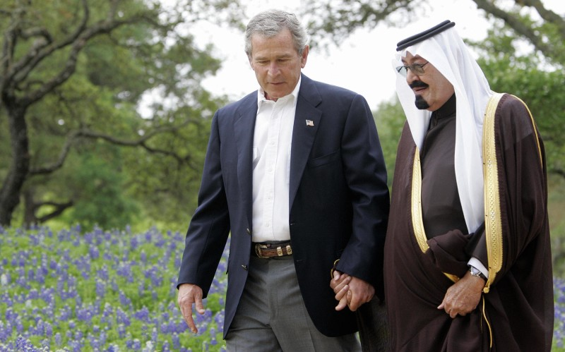 Crawford, UNITED STATES:  (FILES): This 25 April 2005 file photo shows US President George W. Bush (L) holding hands with then Saudi Arabian Crown Prince Abdullah (R) as they walk past a field of blue bonnet flowers at Bush's ranch in Crawford, Texas. Saudi Arabia has advised the Bush administration it may provide financial backing to Iraqi Sunnis against Iraq?s Shiites if the United States withdraws its troops from Iraq, the New York Times said 12 December 2006, quoting American and Arab diplomats. Abdullah, who succceeed his brother Fahd as King,  reportedly conveyed this to US Vice President Dick Cheney two weeks ago in Riyadh.          AFP PHOTO/FILES/Jim WATSON  (Photo credit should read JIM WATSON/AFP/Getty Images)