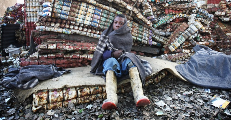 MASERU, LESOTHO - JULY 09:  A young street kid sits on a matteress made from tin cans in Maseru on July 9, 2008 in Maseru, Lesotho. Street children in Mesuru are one of the vulnerable groups being helped by the charity Sentebale. Sentebale was founded by Prince Seeiso from the Lesotho Royal family and Prince Harry from the British Royal family in response to the plight of the neediest of Lesotho's people - its orphans and vulnerable children. Lesotho is a country in desperate need of help, many of the adults have been wiped out by HIV/AIDS leaving a generation of over 380,000 orphans struggling to fend for themselves. The plight of the children in Lesotho is a priority for Prince Harry and his recent trip to the region has highlighted to the world the problems.  (Photo by Chris Jackson/Getty Images)
