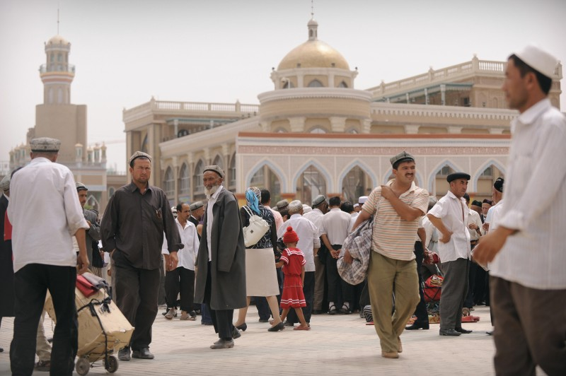 "Ethnic Uighurs gather on Id Kah Square after Friday prayer in the nearby  main mosque on August 8, 2008  in Xinjiang's famed Silk Road city of Kashgar in China's far northwestern, mainly Muslim Xinjiang region. Chinese authorities announced stepped up controls on religious figures and potential ""trouble-makers"" in the Muslim city of Kashgar to guard against attacks on the Beijing Olympics which open today following the deadly attack that killed 16 police officers and a new threat by separatists from China's far northwest Xinjiang region to attack the Games. AFP PHOTO/Peter PARKS (Photo credit should read PETER PARKS/AFP/Getty Images)"