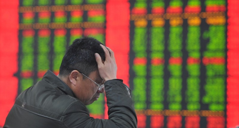A stock investor gestures as he checks share prices at a securities firm in Fuyang, east China's Anhui province on January 19, 2015. Chinese shares plunged on January 19 after regulators punished several brokerages for violating rules for margin trading business, which has fuelled an extended market rally, analysts said.  AFP PHOTO    CHINA OUT        (Photo credit should read STR/AFP/Getty Images)