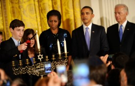 WASHINGTON - DECEMBER 2: (AFP-OUT) U.S. President Barack Obama (2nd R), First Lady Michelle Obama (3rd R) and Vice president Joe Biden (R) watch as Dina Retik lights the second candle of the menorah during a reception for Hanukkah in the East Room of the White House on December 2, 2010 in Washington, DC.  Hanukkah marks the 8-day Jewish celebration of the Festival of Lights. (Photo by Mike Theiler-Pool/Getty Images)