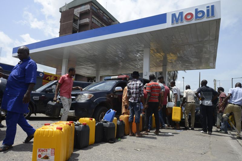 People queue with jerrycans to buy fuel at Mobil filling station in Lagos, on May 21, 2015. Long queues formed at petrol stations across oil-rich Nigeria on May 21 following a row over subsidy payment to petrol importers as well as sale of government oil blocks to private investors, union officials said. AFP PHOTO/PIUS UTOMI EKPEI        (Photo credit should read PIUS UTOMI EKPEI/AFP/Getty Images)
