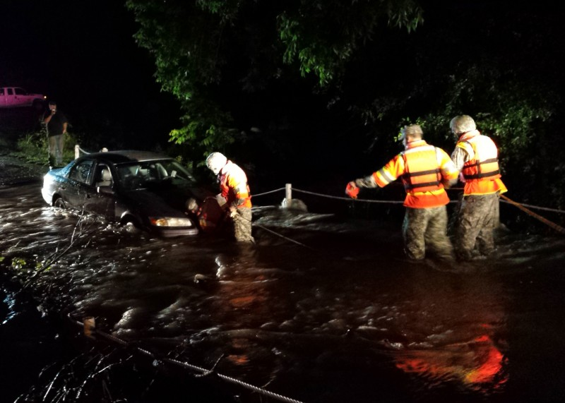 Engineers from the 111th Engineer Battalion, Texas Army National Guard, working with local first responders, rescue three people from a stalled vehicle stuck in a low water crossing May 26, 2015, near Granbury, Texas. Texas Guardsmen rescued more than 100 Texans in need during flooding across the state, mid-late May 2015. (U.S. Army National Guard photo by 1st Lt. Max Perez/ Released)