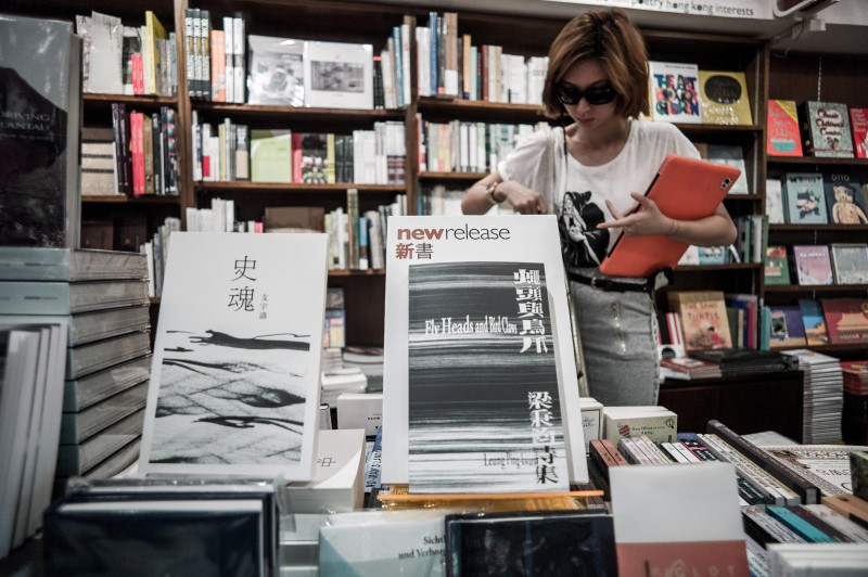 TO GO WITH Lifestyle-China-HongKong-literature,FEATURE by Samantha Kuok Leese In this picture taken on August 20, 2012 a woman browses books in a bookstore of Hong Kong.  A potent mix of state censorship, conservative publishing choices and scant translation means international readers are given a narrow view of contemporary China, industry critics say. AFP PHOTO / Philippe Lopez        (Photo credit should read PHILIPPE LOPEZ/AFP/GettyImages)