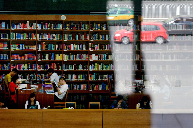 Cars are reflected in a window as people read books at national library in Beijing on May 30, 2013. China's ruling Communist Party has called for greater political instruction for young university teachers, the education ministry has said.                AFP PHOTO/WANG ZHAO        (Photo credit should read WANG ZHAO/AFP/Getty Images)