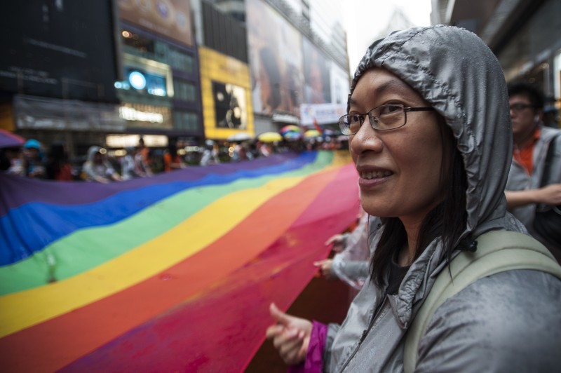 People march in Causeway Bay district during the Gay Pride Parade in Hong Kong on November 8 2014.  The atmosphere was jovial as nearly two thousand people, some wrapped in rainbow-coloured flags and some dressed in drag took to the streets in Hong Kong's Gay Pride parade    AFP PHOTO / XAUME OLLEROS        (Photo credit should read XAUME OLLEROS/AFP/Getty Images)