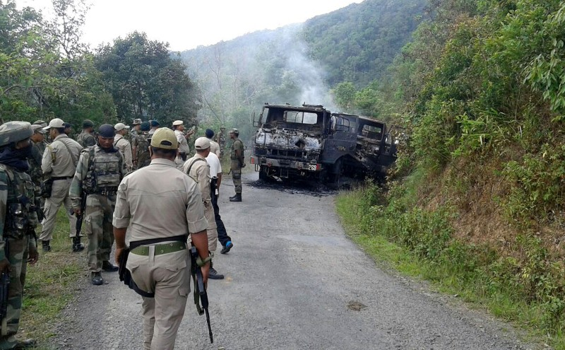In this photograph taken on June 4, 2015, Indian security personnel stand alongside the smouldering vehicle wreckage at the scene of an attack on a military convoy in a remote area of Chandel district, about 120 kilometres (75 miles) southwest of northeastern Manipur's state capital Imphal.  Heavily armed rebels in India's restive northeast killed at least 20 troops on June 4, police said, in one of the area's worst such attacks in years.  AFP PHOTO        (Photo credit should read STR/AFP/Getty Images)