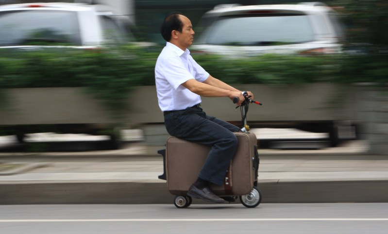 This picture taken on May 28, 2014 shows Chinese farmer He Liangcai riding a motorized scooter suitcase that he invented on the street in Changsha, central China's Hunan province. He has spent the past ten years developing this suitcase that can travel up to 12.5mph, rivaling your average motorized scooter, state media reported.   CHINA OUT     AFP PHOTO        (Photo credit should read STR/AFP/Getty Images)