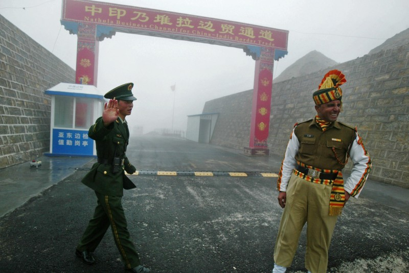 TO GO WITH STORY BY PARUL GUPTA 'INDIA-CHINA-DIPLOMACY-TRADE'  In this photograph taken on July 10, 2008 a Chinese soldier (L) and an Indian soldier stand guard at the Chinese side of the ancient Nathu La border crossing between India and China.  When the two Asian giants opened the 4,500-metre-high (15,000 feet) pass in 2006 to improve ties dogged by a bitter war in 1962 that saw the route closed for 44 years, many on both sides hoped it would boost trade. Two years on, optimism has given way to despair as the flow of traders has shrunk to a trickle because of red tape, poor facilities and sub-standard roads in India's remote northeastern mountainous state of Sikkim.  AFP PHOTO/Diptendu DUTTA (Photo credit should read DIPTENDU DUTTA/AFP/Getty Images)