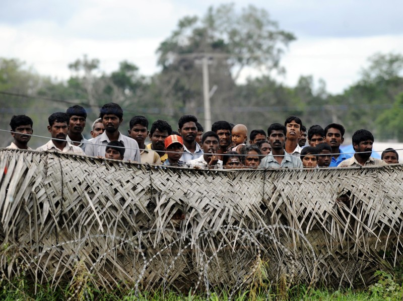 Sri Lankan war-displaced civilians peer from behind barbed wire fences surrounding their internment camp in Vavuniya on November 21, 2009. Sri Lanka said it plans to allow some 136,328 war-displaced civilians to come and go freely from their camps from December 1 with resettlement completed by January 31, 2010. Some 288,000 people were displaced when the conflict with separatist Tamil Tigers ended in May. AFP PHOTO/Ishara S. KODIKARA (Photo credit should read Ishara S. KODIKARA/AFP/Getty Images)