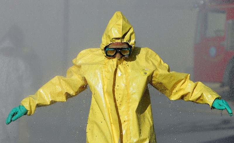 COLMA, CA - FEBRUARY 1:  A man wearing a hazardous materials suit walks through a decontamination shower during a weapons of mass destruction training workshop February 1, 2005 in Colma, California. Representatives from several San Mateo County police and fire departments took part in the one day training to prepare for a chemical or biological attack.  (Photo by Justin Sullivan/Getty Images)