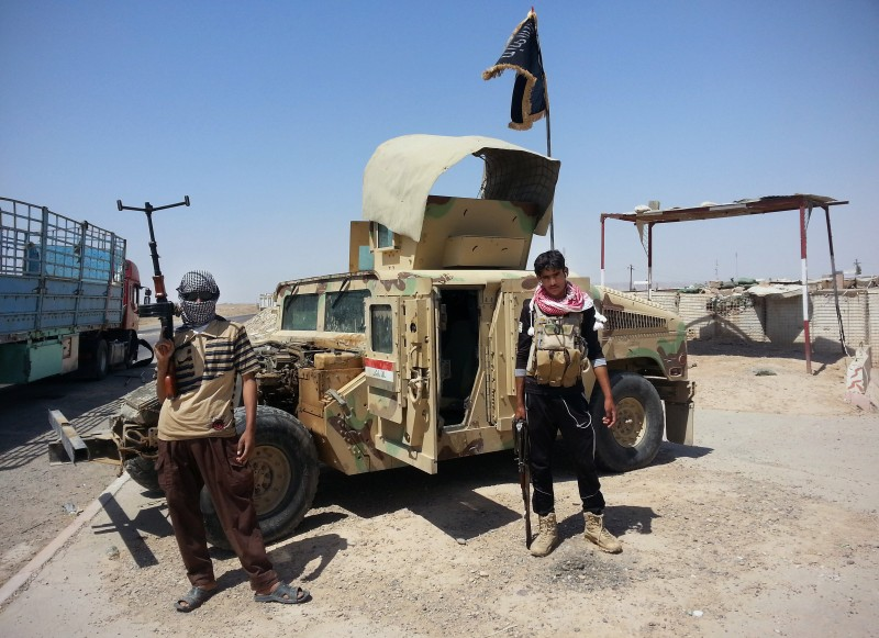 FILE - In this file photo taken Thursday, June 19, 2014, Islamic State group militants stand with a captured Iraqi army Humvee at a checkpoint outside Beiji refinery, some 250 kilometers (155 miles) north of Baghdad, Iraq. It took 30 days as Lt. Gen. Abdul-Wahab al-Saadi's force made an agonizingly slow journey for 40 kilometers (25 miles) through roadside bombs and suicide car attacks, then successfully laid siege to the oil refinery city of Beiji. The campaign earned al-Saadi the biggest battlefield victory by Iraqi forces since the military collapsed as Islamic State fighters swept over most of northern and western Iraq in a summer blitz. (AP Photo, File)