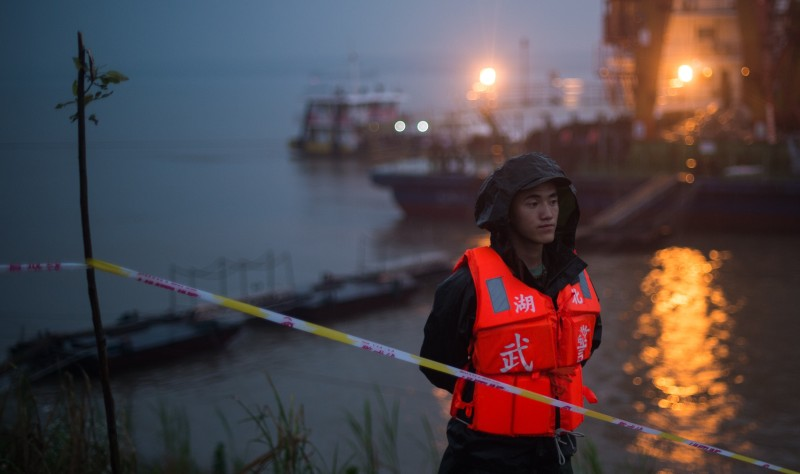 """A Chinese soldier stands guard near the unseen capsized passenger ship Dongfangzhixing or """"Eastern Star"""" vessel which sank in the Yangtze river in Jianli, central China's Hubei province on June 2, 2015. Divers raced to find survivors on June 2 after a Chinese ship sank with more than 450 mainly elderly people in the storm-tossed Yangtze river, raising hopes more people can be found alive.  AFP PHOTO / JOHANNES EISELE        (Photo credit should read JOHANNES EISELE/AFP/Getty Images)"""