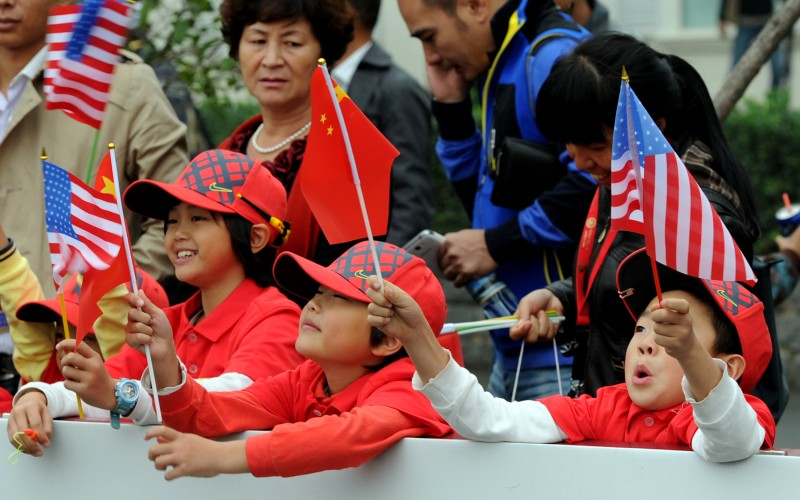 TO GO WITH US-vote-China,FOCUS by Sebastien Blanc Chinese children wave their national flag together with the US flags as they attend the one-day golf challenge between Tiger Woods of the US and Rory McIlroy of Northern Ireland in Zhengzhou, in central China's Henan province on October 29, 2012.  The world's two biggest economies choose their next leaders in early November, an accident of timing that puts China's opaque communist state and America's riotous democracy in stark contrast.           AFP PHOTO/GOH CHAI HIN        (Photo credit should read GOH CHAI HIN/AFP/Getty Images)