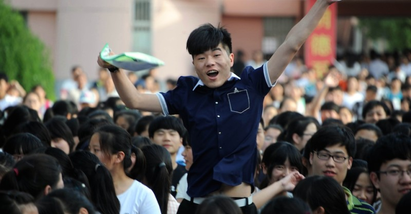 This picture taken on June 8, 2015 shows a high school reacting as they walk out of a school after sitting the 2015 national college entrance examination, or the ''Gaokao'', in Bozhou, east China's Anhui province. Nearly 10 million high school students sat for China's make-or-break college entrance exams under tight security on June 7 to 8.  AFP PHOTO   CHINA OUT        (Photo credit should read STR/AFP/Getty Images)