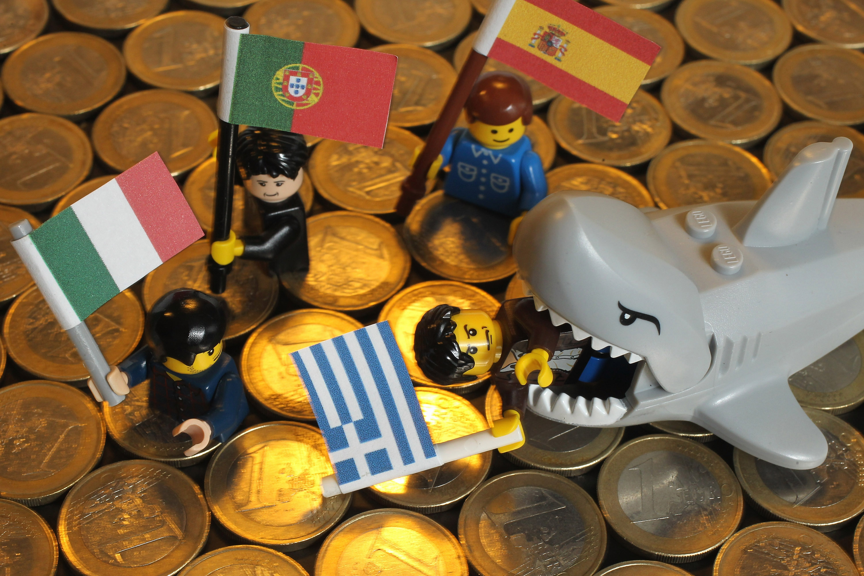 BERLIN, GERMANY - SEPTEMBER 27: In this photo illustration a Lego shark chomps down on a Lego figure holding a Greek flag as other figures holding an Italian (L), Portuguese (C) and Spanish flag look on over a sea of Euro coins on September 27, 2011 in Berlin, Germany. Europe is continuing to wrestle with the ominous prospect of a Greek debt default that many fear could spread panic and push the already fragile economies of Italy, Portugal and Spain into a Eurozone crisis with global repercussions.  (Photo by Sean Gallup/Getty Images)