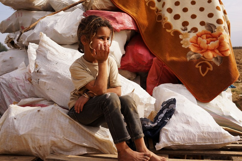 MAJDAL ANJAR, LEBANON - NOVEMBER 12: A Syrian girl sits on bags of firewood in a makeshift camp for Syrian refugees only miles from the border with Syria in the Bekaa Valley on November 12, 2013 in Majdal Anjar, Lebanon. As the war in neighboring Syria drags on for a third year, Lebanon, a country of only 4 million people, is now home to the largest number of Syrian refugees who have fled the conflict. The situation is beginning to put huge social and political strains on Lebanon as there is currently no end in sight to the war in Syria. (Photo by Spencer Platt/Getty Images)