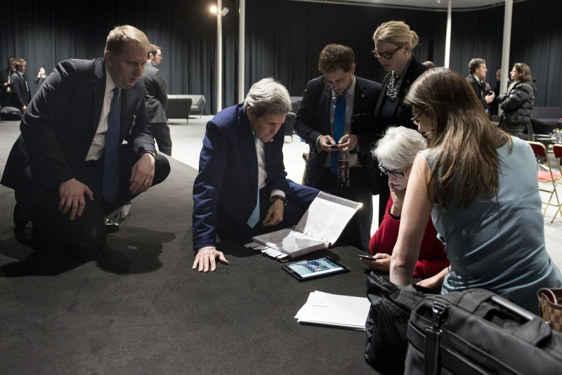 US Secretary of State John Kerry (2nd L) watches on a tablet as the US president addresses the US, at the Swiss Federal Institute of Technology in Lausanne (Ecole Polytechnique Federale De Lausanne) on April 2, 2015, after Iran nuclear program talks finished with extended sessions. European powers and Iran on April 2 hailed a breakthrough in talks on reaching a deal to curtail Tehran's nuclear programme. AFP PHOTO / POOL / BRENDAN SMIALOWSKI        (Photo credit should read BRENDAN SMIALOWSKI/AFP/Getty Images)