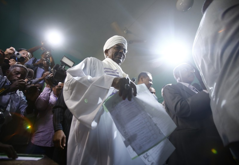 Sudanese President and candidate in the presidential elections Omar al-Bashir (C) casts his vote at a polling station in the Saint Francis school in the capital, Khartoum, on April 13, 2015. With 15 little-known candidates running against him, 71-year-old Bashir faces no real competition in the second contested vote since he seized power in 1989.  AFP PHOTO / ASHRAF SHAZLY        (Photo credit should read ASHRAF SHAZLY/AFP/Getty Images)