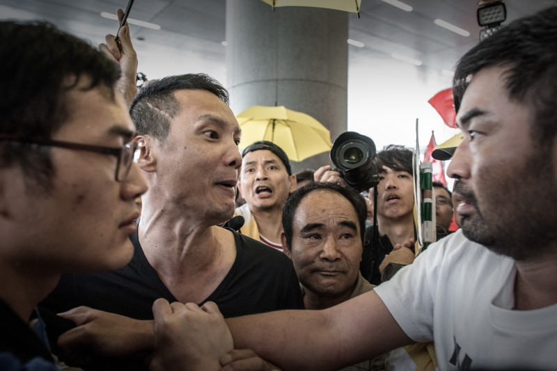 A pro-Beijing protester (L) argues with a pro-democracy demonstrator (R) outside the government building in Hong Kong on April 22, 2015.  Hong Kong's government announced a roadmap for leadership elections which offered no concessions to the city's democracy camp -- prompting opposition lawmakers to walk out of the plan's unveiling.  AFP PHOTO / Philippe Lope8        (Photo credit should read PHILIPPE LOPEZ/AFP/Getty Images)