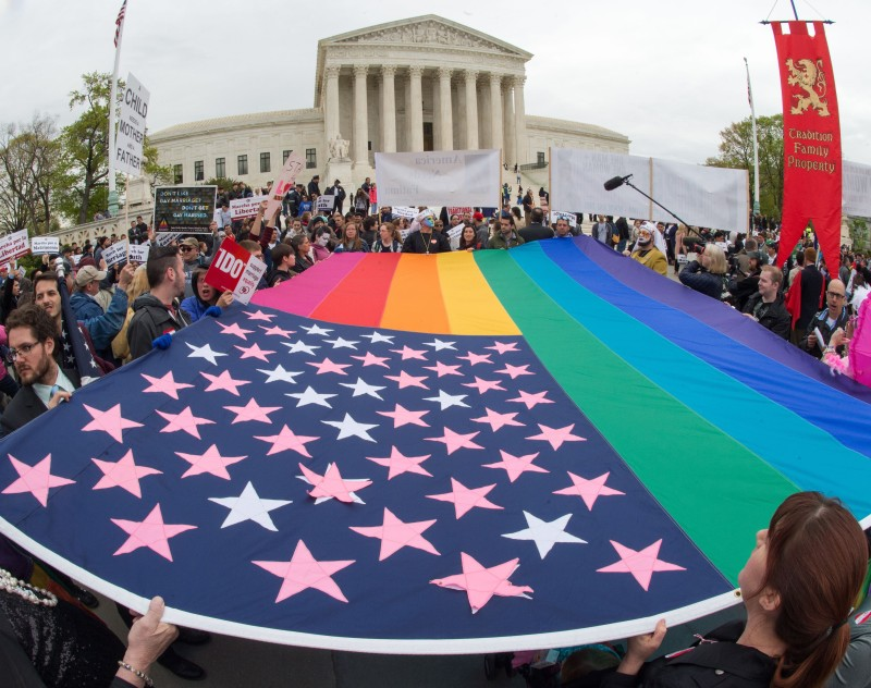 Protesters hold a pro-gay rights flag outside the US Supreme Court on April 25, 2015, countering the demonstrators who attended the March For Marriage in Washington, DC. The Supreme Court meets on April 28 to hear arguments whether same-sex couples have a constitutional right to wed in the United States, with a final decision expected in June.       AFP PHOTO/PAUL J. RICHARDS        (Photo credit should read PAUL J. RICHARDS/AFP/Getty Images)